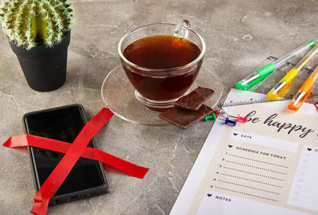 Unplugging concept, mobile phone crossed out with a red ribbon, coffee with chocolate and colored pens, diary sheets with an inscription.