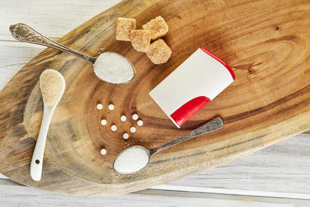 Sugar substitute tablets and natural sweetener in powder and brown, white and diced sugar on a wooden stand. Flat lay. Copy space for text.