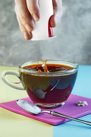 Male hand throwing sugar substitute pills into a cup of coffee and splash on purple podium.