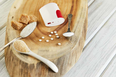 Sugar substitute tablets and natural sweetener in powder and brown, white and diced sugar on a wooden stand. Copy space for text.