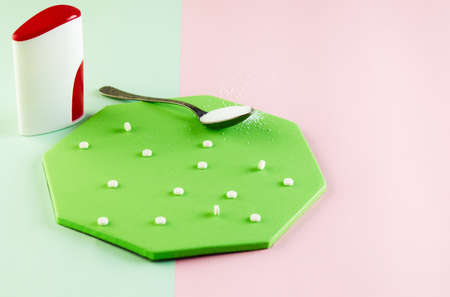 Sugar substitute tablets and natural sweetener powder on a green podium. Copy space for text.