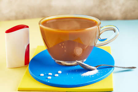 A cup of coffee and Pills of sugar substitute and natural sweetener in powder on a yellow and blue podium.