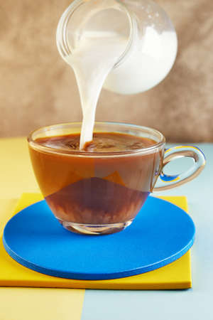 A cup of coffee and milk flowing into a cup on a yellow and blue podium.