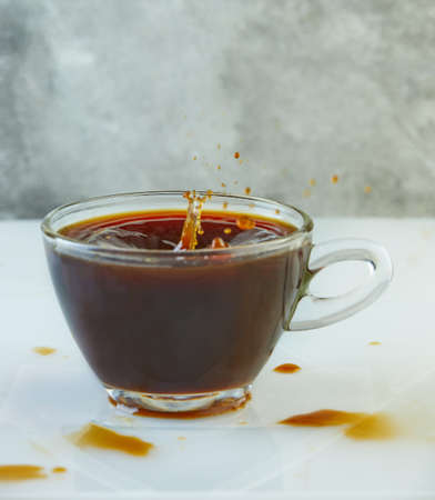 Splash of coffee in a cup with a drink on a gray-white background.