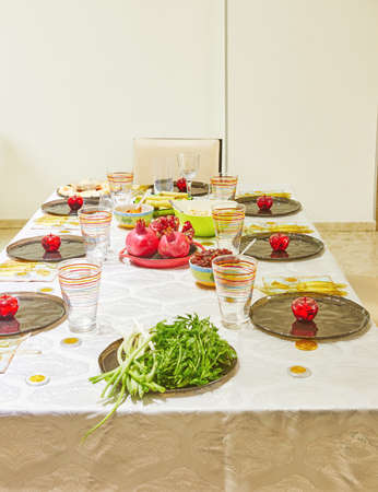 Festively decorated table for Rosh Hashanah with pomegranates and apples.