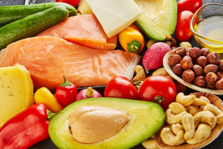 Ketogenic diet concept. Low carb keto diet food set. Green vegetables, nuts, fish fillets, cherry tomatoes. Healthy food concept. Zdjęcie Seryjne