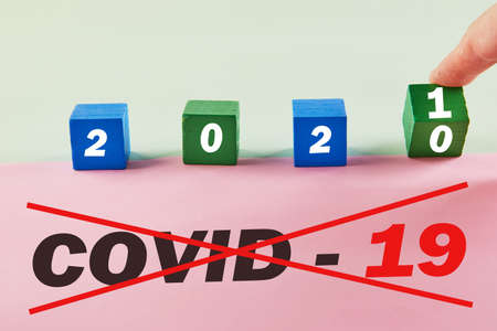 The hand turns the cube and changes the year 2020 from Covid-19 to 2021 without coronavirus.