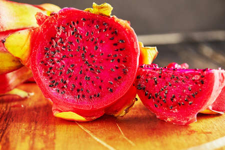 Dragon fruit - pitahaya Cut into pieces on a wooden stand on a black wooden background.