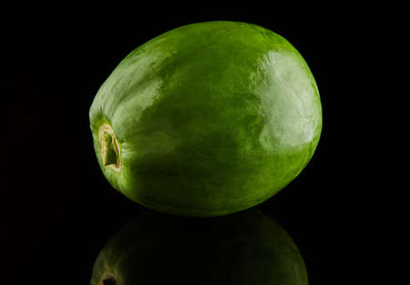 Green round papaya on a black background with reflection.