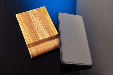Wooden desktop mobile phone holder with hand-held phone isolated on blue black background. Creativity and technology concept.