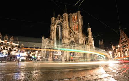 Lights of moving tram on night city Gent