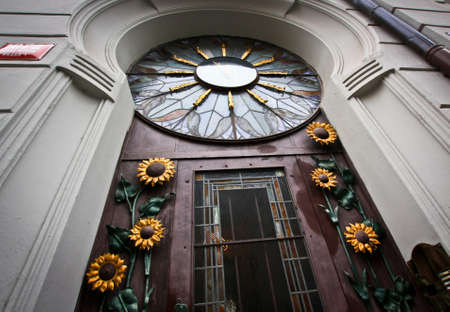Street door decorated with sunflowers and clock