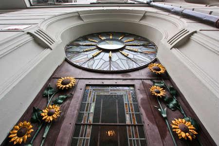 Strassentür mit Sonnenblumen und Uhr verziert Standard-Bild - 71639190