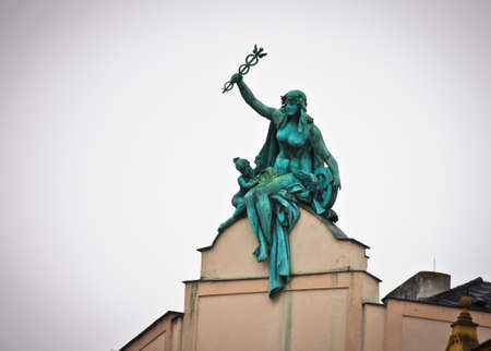 Bronze statue of woman with a rod of Mercury on the roof Standard-Bild