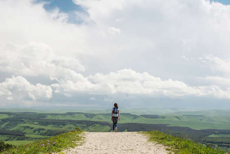 The girl goes to the horizon against the sky Stock Photo