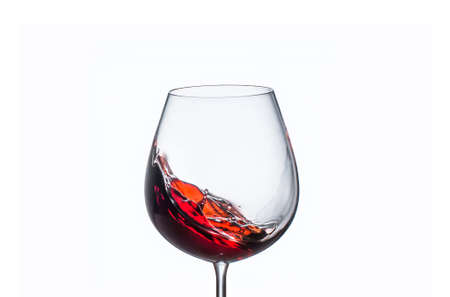 Splashing red wine in a glass on a white background