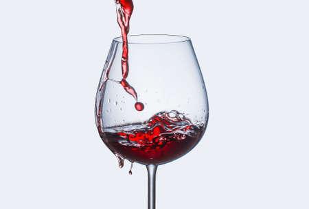 Verter vino tinto en un vaso con salpicaduras Foto de archivo