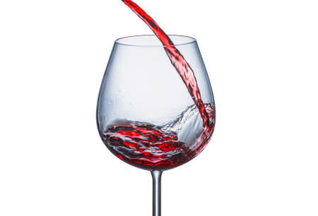 Pouring red wine into a glass with splashes on a white background
