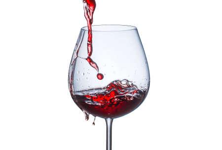 Verter el vino tinto en un vaso con salpicaduras sobre un fondo blanco.