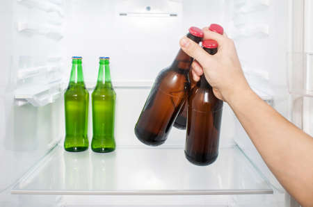 A man's hand takes out three bottles of beer from the refrigerator. close-up