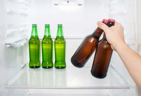 A man's hand takes out two bottles of beer from the refrigerator. close-up