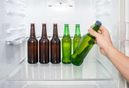 A man's hand takes out bottles of beer from the refrigerator. close-up