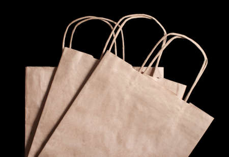 3 paper brown bags on a black background. View from above Banco de Imagens