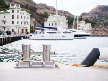 Anchorages for mooring of ships at the pier on the background of beautiful yachts and mountains Standard-Bild