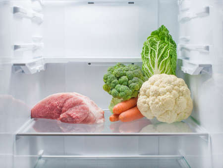 Fresh meat and fresh vegetables opposite each other in an empty refrigerator. The choice between vegetarianism and meat-eating