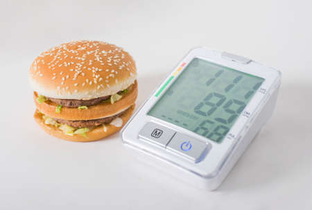 Hamburger and pressure gauge on a white background. Health effects of junk food