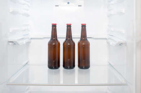 Brown glass beer bottles stand on a shelf in the refrigerator