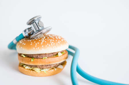 Hamburger and medical stethoscope on a white background, copy space. Health effects of junk food