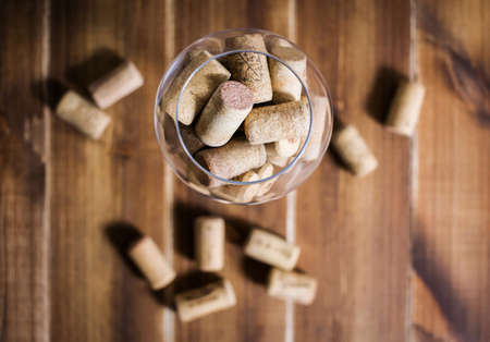 Many wine corks in the glass on the table. View from above