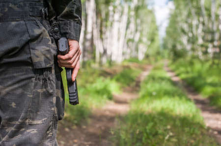 A man in military clothes holds a gun in his hand. Close-up on a background of a summer forest and road. Back view