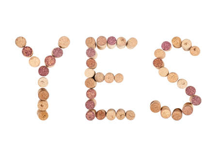 The word YES is made from wine corks. Isolated on white background Фото со стока