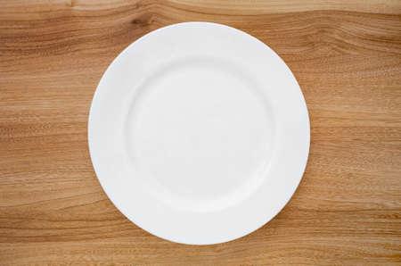 Assiette blanche ronde sur une table en bois. Vue d'en-haut