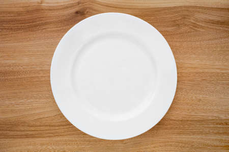 Round white plate on a wooden table. View from above