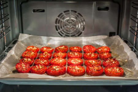Lots of chopped sun-dried tomatoes with spices, garlic and olive oil in the oven Banque d'images