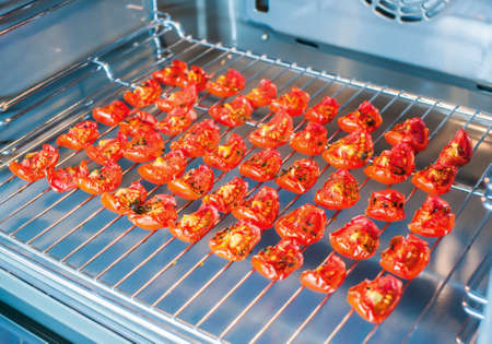 Slices of sun-dried tomatoes on a wire rack in the oven. Overall plan
