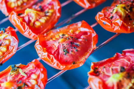 Slices of sun-dried tomatoes with spices on a metal wire rack in the oven. Close-up. Macro Archivio Fotografico