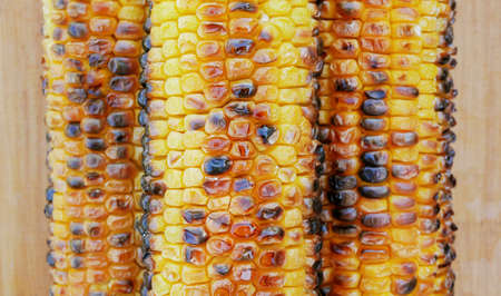 Three ripe fried corn lie side by side on a wooden background. View from above. Macro