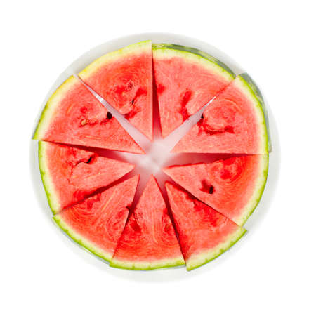 Triangular slices of ripe red watermelon on a white plate. Isolated on white background. View from above