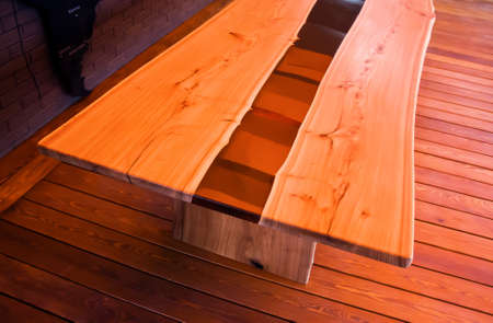 Large long wooden table with epoxy fill in the evening in a modern loft style home interior. View from above Zdjęcie Seryjne