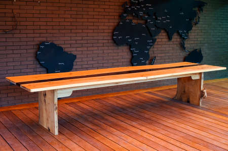 Large long wooden table with epoxy fill in the evening in a modern loft-style home interior