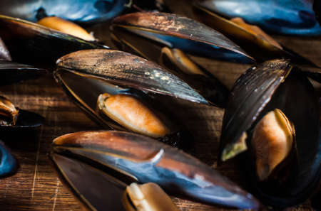 Mussels in shells on a wooden background. Close-up, top view Stock fotó