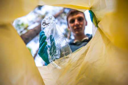 Garbage collection in nature. Young man puts plastic trash in a yellow bag, inside view