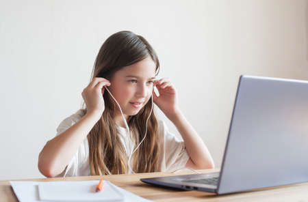 Little girl smiles and waves her hand while sitting at home at the table with a laptop. Online communication, distance learning