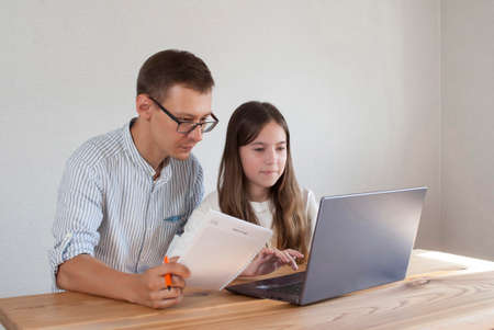 Young dad helps little daughter schoolgirl on distance learning sitting at table with computer at home