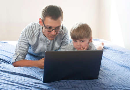 Young dad and little son are lying on the bed and looking at a laptop. Father teaches his son at home on the computer. Modern upbringing and education. front view