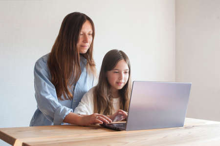 Young mother helping her daughter schoolgirl on distance learning session at home at table with laptop Stock fotó